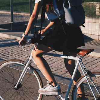Young woman cycling with sunset